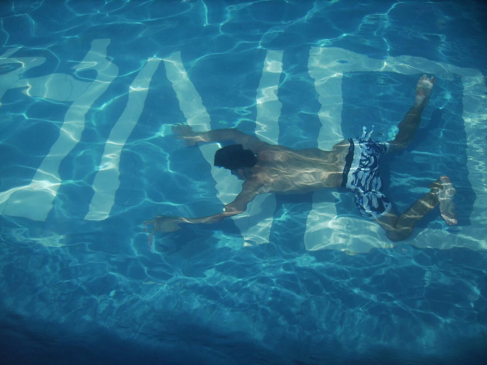 プールで平泳ぎする男性
